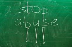 Las palabras PARAN EL ABUSO escrito en el consejo escolar verde imagen de archivo
