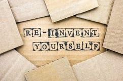 Las palabras se reinventan hacen por los sellos negros del alfabeto en cardbo imagen de archivo libre de regalías