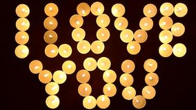Las palabras TE AMO formaron por las velas que brillaban intensamente y adornado con las flores