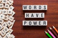 Las palabras tienen accionar el cubo de la palabra en el fondo de madera, concepto del aprendizaje de idiomas ingleses imagen de archivo libre de regalías