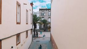 Las Palmas de Gran Canaria, Spanien - 23. April 2019: Vogelperspektive - junges stilvolles Mädchen, das entlang eine schmale Stra stock video footage