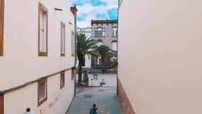 Las Palmas de Gran Canaria, Spanje - April 23, 2019: Satellietbeeld - jong modieus meisje die langs een smalle straat lopen van stock videobeelden