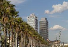 Las palmas en Barcelona varan con el monumento de oro de los pescados en el backgr Fotografía de archivo libre de regalías