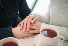 Las palmas femeninas mienten en los hombres al lado de dos tazas de té Foto de archivo