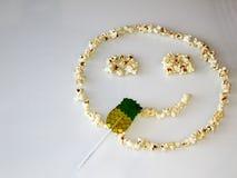 Las palomitas presentaron en la forma de un smiley, en un fondo blanco imagen de archivo libre de regalías