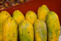 Las papayas maduras con la piel amarilla exhibida en la tabla roja en una fruta almacenan Depok admitido foto Indonesia Imagenes de archivo