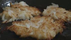 Las papitas fritas ligeramente fritas con la corteza de oro se fríen en una cacerola en cambio del foco del aceite metrajes