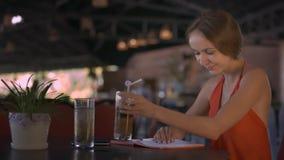 Las paradas de la muchacha que escriben en diario beben el jugo en café