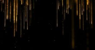 Las partículas de oro de la chispa del brillo fluyen el bokeh que fluye del top y abajo en fondo negro, la Navidad del oro y la F