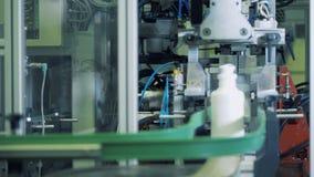 Las partes inferiores de las botellas plásticas blancas están consiguiendo cortadas por el mecanismo almacen de video