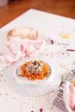 Las pastas anaranjadas y la salsa blanca sirvieron en la placa blanca Imagen de archivo