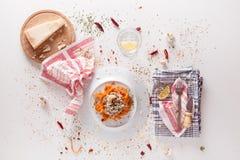 Las pastas anaranjadas y la salsa blanca sirvieron en la tabla blanca Foto de archivo libre de regalías