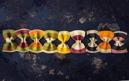 Las pastas bajo la forma de raya coloreada arquean la raya alineada en un fondo oscuro Lugar para el texto Fondo El marco horizon Fotos de archivo libres de regalías