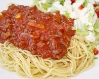 Las pastas cocinadas de los espaguetis remataron con una salsa hecha en casa deliciosa de la carne y una ensalada fresca del lado Fotografía de archivo libre de regalías