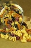 Las pastas crudas desbordan el tarro de cristal Foto de archivo libre de regalías