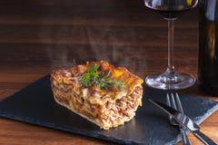 Las pastas de cocido al vapor al vapor calientes frescas de las lasañas de la comida italiana sirvieron en la tabla y la placa de Fotos de archivo libres de regalías