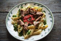 Las pastas de Penne en salsa de tomate con el pollo, tomates adornaron el perejil Imagen de archivo