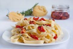 Las pastas del Fettuccine con los tomates secados al sol y las hierbas frescas están mintiendo en una placa blanca Objeto aislado fotografía de archivo