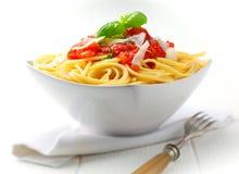 Cuenco de pastas con la salsa de tomate y la albahaca fresca imagen de archivo