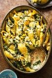 Las pastas enormes de la concha marina de la espinaca con parmesano y el queso verde cuecen fotos de archivo