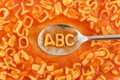 Las pastas formaron las letras de ABC en salsa de tomate en una cuchara Fotos de archivo