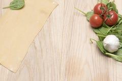 Las pastas frescas cubren con las hojas del tomate, del ajo y de la espinaca Foto de archivo libre de regalías