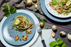 Las pastas verdes de la espinaca con las verduras proliferan rápidamente los huevos del tost y de codornices del trigo imágenes de archivo libres de regalías