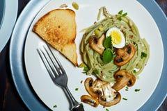 Las pastas verdes de la espinaca con las verduras proliferan rápidamente los huevos del tost y de codornices del trigo imagen de archivo libre de regalías