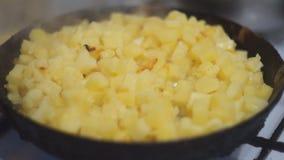 Las patatas cortadas en cuadritos se fríen en una cacerola en un primer de la estufa de gas almacen de video