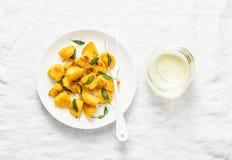 Las patatas curruscantes de la corteza del polenta cocieron con mantequilla sabia y un vidrio de vino blanco en un fondo ligero Imágenes de archivo libres de regalías