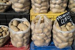 Las patatas en las bolsas de plástico en un mercado griego atascan Imágenes de archivo libres de regalías