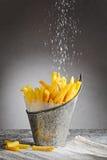 Las patatas fritas asperjadas con la sal en un hierro bucket fotos de archivo libres de regalías
