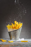 Las patatas fritas asperjadas con la sal en un hierro bucket Imagenes de archivo