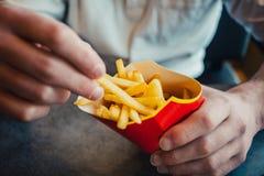 Las patatas fritas se cierran para arriba en las manos del hombre Imagen de archivo libre de regalías