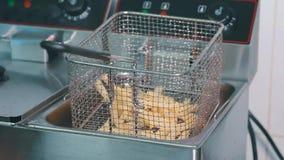 Las patatas fritas se fríen en el restaurante almacen de video