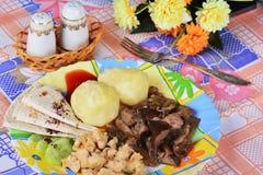 Las patatas hervidas con el pollo cortan pedazos y setas fritas Imagenes de archivo