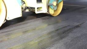Las pavimentadoras y los rodillos reparan la carretera de asfalto en una ciudad almacen de metraje de vídeo