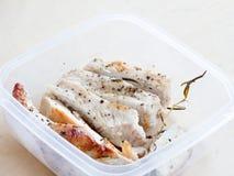 Las pechugas de pollo asadas a la parrilla con pimienta negra y la rosa casan la hoja en un envase de plástico Imagen de archivo