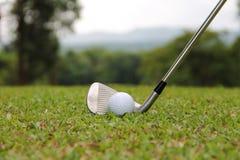 Las pelotas de golf y los clubs de golf están en el campo de golf Foto de archivo
