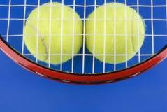 Las pelotas de tenis están bajo una raqueta de tenis en un azul Fotografía de archivo libre de regalías