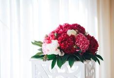 Las peonías abandonan en el restaurante, ajuste de la tabla Decoración de la boda Flores rojas en el restaurante foto de archivo libre de regalías