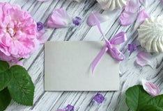 Las peonías blancas florecen con la tarjeta de felicitación vacía en un fondo de madera blanco - imagen común Foto de archivo