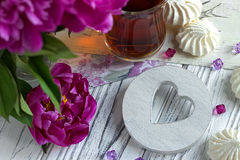 Las peonías florecen el vidrio rosado de té con la melcocha de madera blanca en un fondo de madera blanco - imagen común del cora Fotografía de archivo
