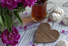 Las peonías florecen el vidrio rosado de té con la melcocha de madera marrón en un fondo de madera blanco - imagen común del cora Imagenes de archivo