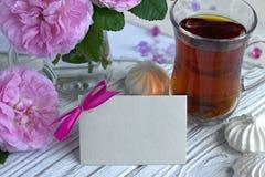 Las peonías florecen el vidrio rosado de té con la melcocha en un fondo de madera blanco - imagen común de la tarjeta de felicita Imagenes de archivo