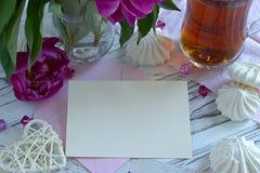 Las peonías florecen el vidrio rosado de té con la melcocha en un fondo de madera blanco - imagen común de la tarjeta de felicita Foto de archivo