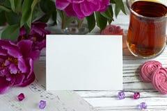 Las peonías florecen el vidrio rosado de té con la melcocha en un fondo de madera blanco - imagen común de la tarjeta de felicita Imagen de archivo