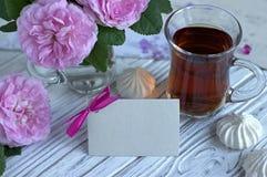 Las peonías florecen el vidrio rosado de té con la melcocha en un fondo de madera blanco - imagen común de la tarjeta de felicita Foto de archivo libre de regalías