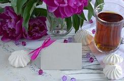 Las peonías florecen el vidrio rosado de té con la melcocha en un fondo de madera blanco - imagen común de la tarjeta de felicita Fotografía de archivo libre de regalías