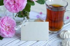 Las peonías florecen el vidrio rosado de té con la melcocha en un fondo de madera blanco - imagen común de la tarjeta de felicita Fotografía de archivo